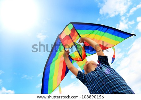 Little boy flies a kite into the blue sky - stock photo