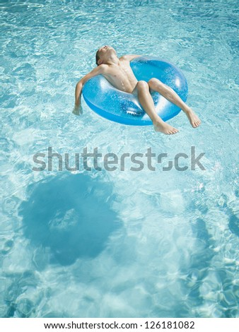 Little boy floating on swim ring in pool - stock photo