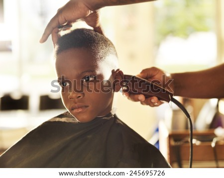 little boy getting his head shaved by barber - stock photo