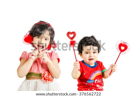 Little boy & girl posing with love symbol isolated in white background - stock photo