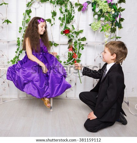 Little boy gives a rose to girl. Little beautiful couple. First love. - stock photo