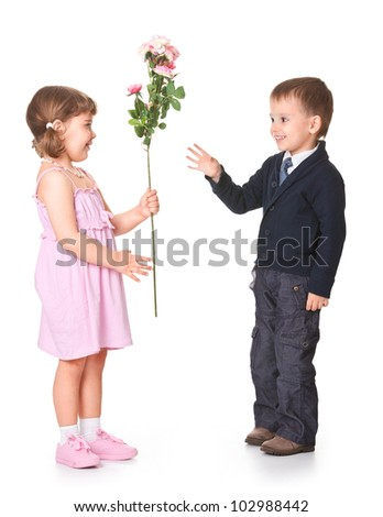little boy gives girlfriend flowers, behind a white background - stock photo