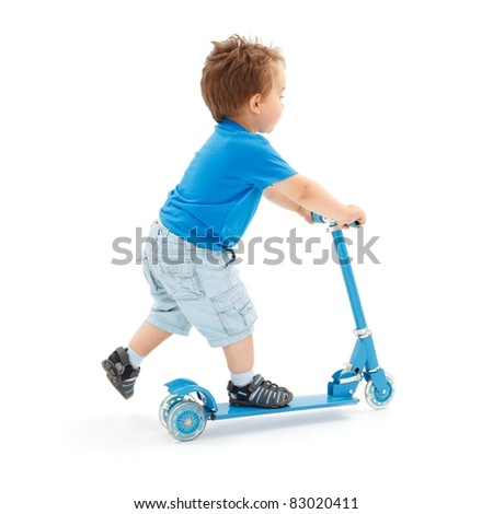 Little boy going fast with toy scooter (partial motion blur on leg) - stock photo