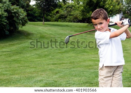 Little boy golfer swinging a club on the golf course