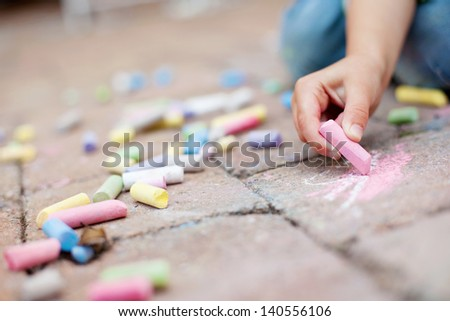 Little boy hands painting on the pavement using a colorful chalk - stock photo
