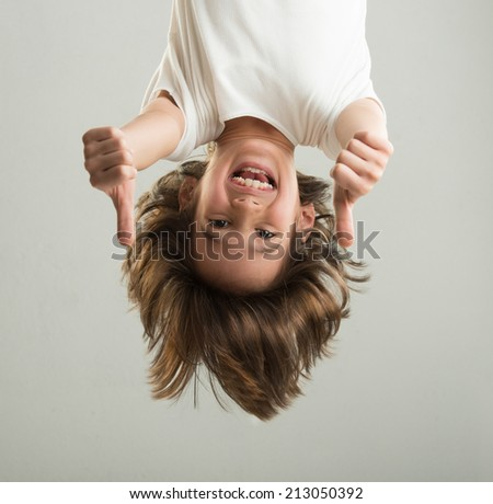 Little boy hanging upside down - stock photo