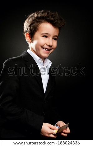 Little boy happy businessman portrait in low key counting money - stock photo