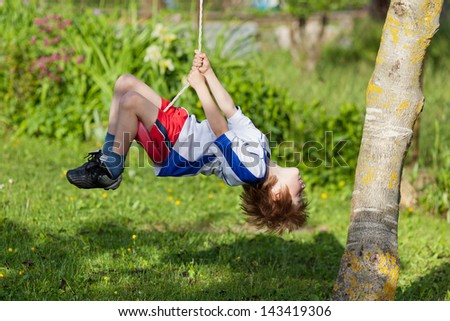 Little boy having a ball on a swing in the park - stock photo