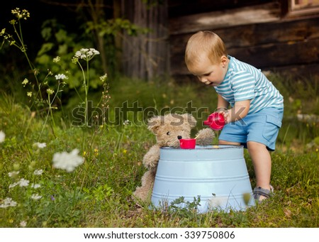 Little boy having a tea party with his friend teddy bear outdoors - stock photo