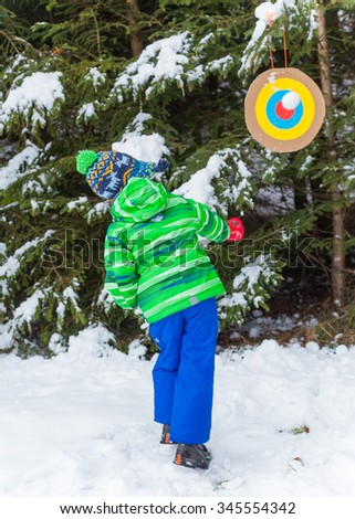Little boy having fun in the snow forest - stock photo