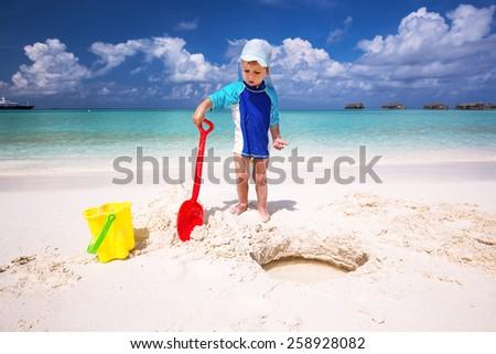 Little boy having fun on the beach while building a sand castle - stock photo