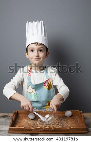 Little boy having fun  playing with cooking utensils on grey background