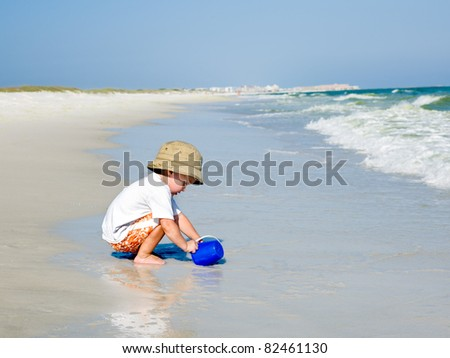 Little boy having fun playing with water by the ocean