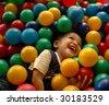 Little boy having fun time in balls pool - stock photo