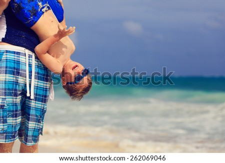 little boy having fun with father on summer tropical beach - stock photo