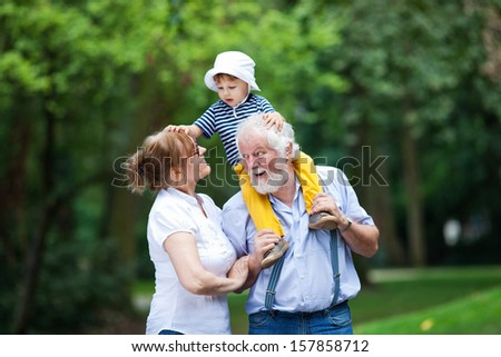 Little boy having fun with his grandparents in park - stock photo