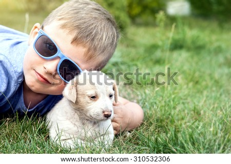Little boy having fun with puppy, summer day. Outdoor photo. - stock photo