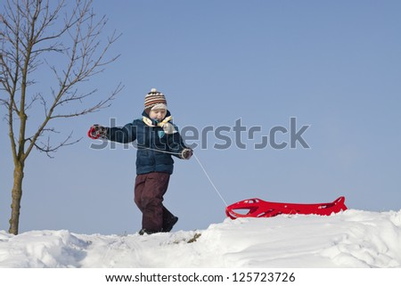Little boy having fun with sledge on a snowy hill - stock photo