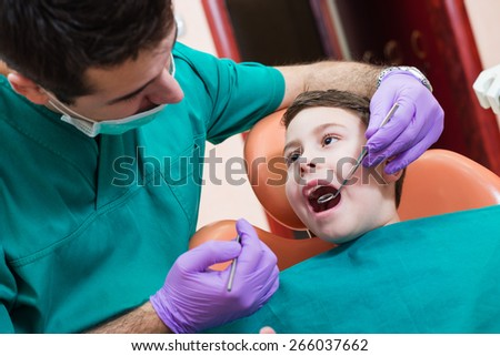 Little boy having his teeth examined by a dentist - stock photo