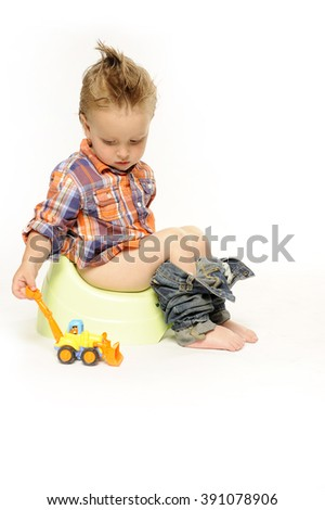 Little boy having lowered jeans sits on a chamber-pot playing with a toy excavator, white background 4.