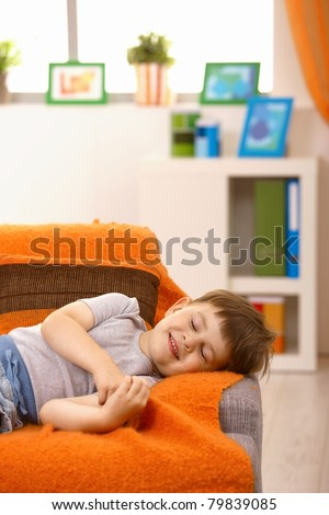 Little boy having nap, smiling in his sleep on couch in living room.? - stock photo