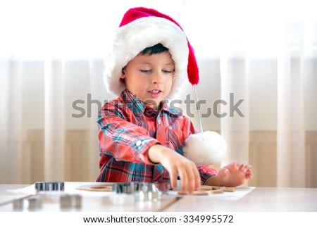 Little boy helping at kitchen with baking cookies, Merry Christmas - stock photo