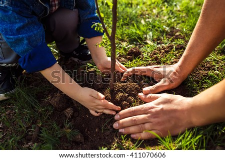 little boy helping his father to plant the tree while working together in the garden. sunday. smiling face. spring time. Love and protect nature concept  - stock photo