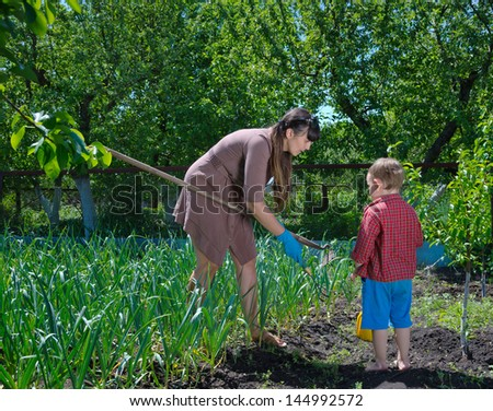 Little boy helping his mother in the garden as she hoes and weeds the vegetable patch