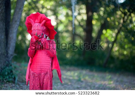 Little boy hiding outside in a dragon costume