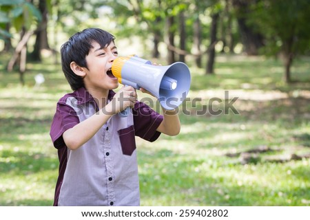 Little boy hold and shouting through megaphone in park - stock photo