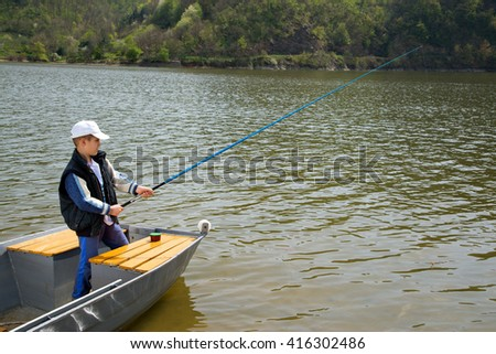 Little Boy Holding A Fishing Rod And Fishing From Wooden Boat On The Lake, Lake Water Rippling  - stock photo