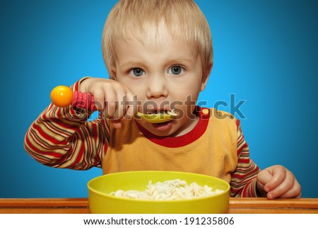 Little boy holding a spoon eats noodles on a blue background.