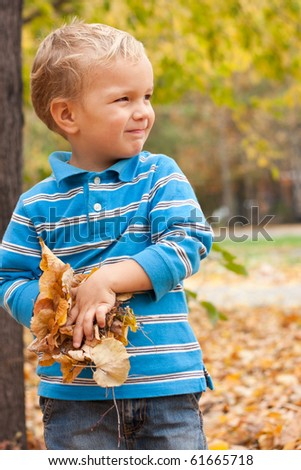 Little boy holding a yellow leaves, autumn. - stock photo