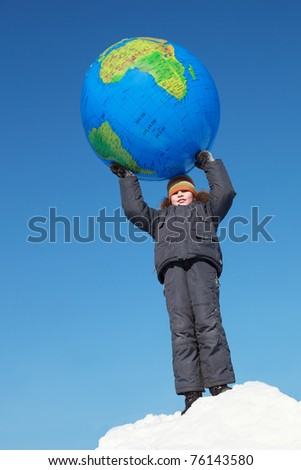 little boy holding big inflatable globe above his head at outdoors in winter