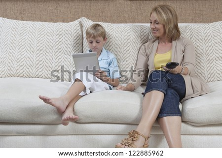 Little boy holding digital tablet while sitting on sofa with his mother