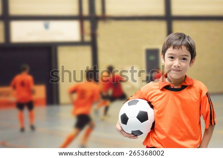 Little boy holding football in gym - stock photo