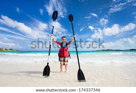 Little boy holding kayak paddles at beach - stock photo