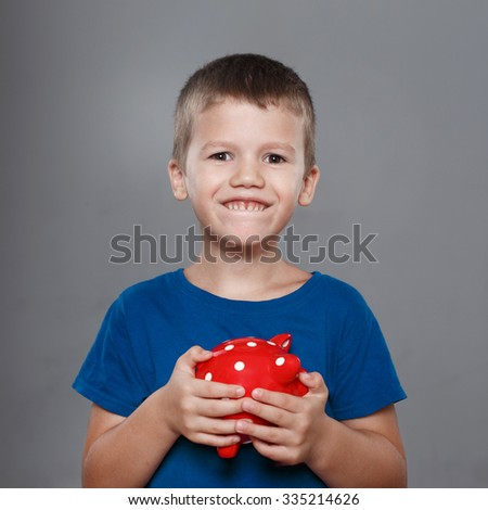 Little boy holding red dotted piggy bank - stock photo