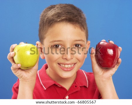 Little boy holding two fresh apples on blue background. - stock photo