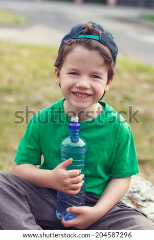 Little boy holding water bottle, outdoor portrait - stock photo
