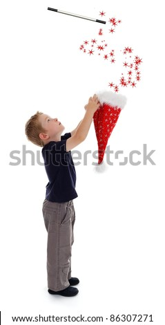 Little boy holding wizard hat, stars pouring out from hat, driven by magic wand - stock photo