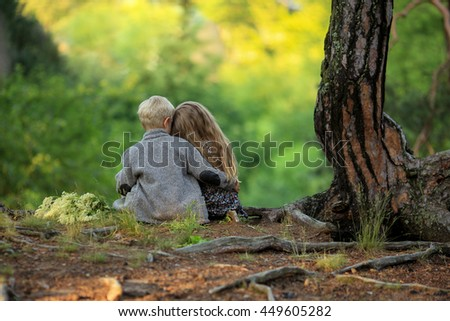 little boy hugging a girl sitting in the woods
