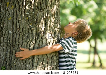 Little boy hugging a tree. Concept: care of nature - stock photo