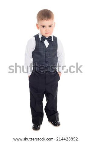 Little boy in a business suit holding his hands in his trouser pockets.