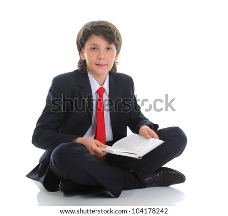 little boy in a business suit reading a book sitting on the floor. Isolated on white background - stock photo