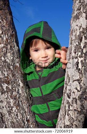 Little boy in a green hood stands among the trees - stock photo