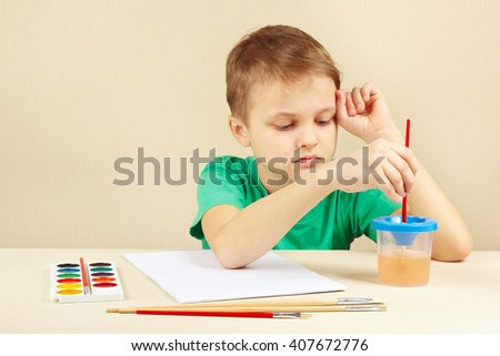Little boy in a green shirt going to paint colors - stock photo
