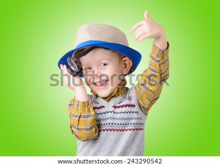 little boy in a hat and glasses on green background