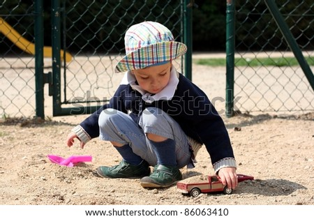 Little boy in a hat plays with toy and car - stock photo