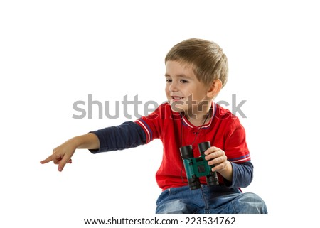 Little boy in a red sweater sits and holds children binoculars pointing finger to the side isolated on white background - stock photo